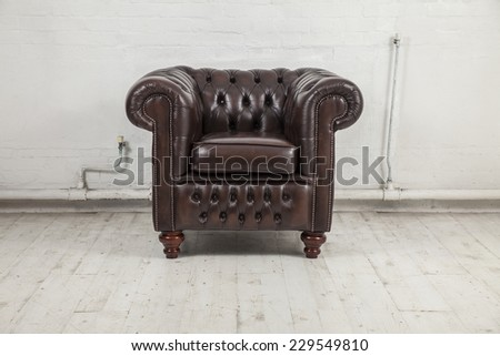 brown vintage chesterfield armchair against white painted brick wall - stock photo