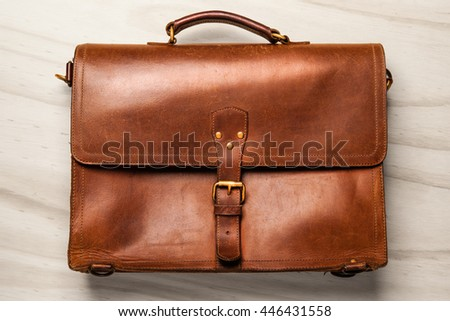 Brown Vintage leather briefcase with strap and brass buckle on wooden background, - stock photo