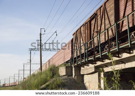 Brown wagons of a freight train in motion go to horizon above metal concrete bridge against blue summer sky with clouds on background   - stock photo