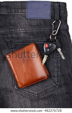 Brown wallet, car keys on black jean.