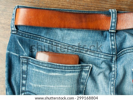 Brown wallet in back blue jeans and brown leather belt - stock photo
