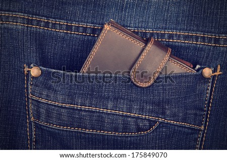Brown wallet in the blue jeans pocket - stock photo