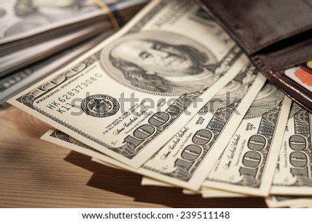 Brown Wallet with credit cards and dollar banknotes over wooden background. Money close-up. Shallow depth of field. - stock photo