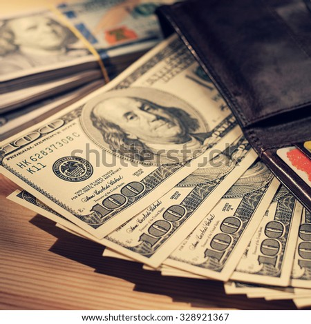 Brown Wallet with credit cards and one hundred dollars banknotes. Shallow depth of field. Retro vintage filtered hipster color image. Creative business finance making money concept .