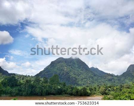 Brown water from mountain, sky and clouds, U-shaped mountains