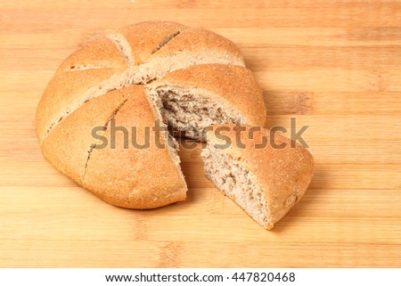 Brown Wheat bread whole meal grain loaf round on wooden background - stock photo