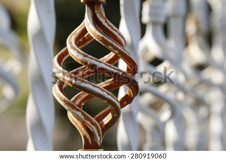 Brown white forged fence inserts close up. Forge Detail. Part of a wrought iron fence. Iron gate details. - stock photo