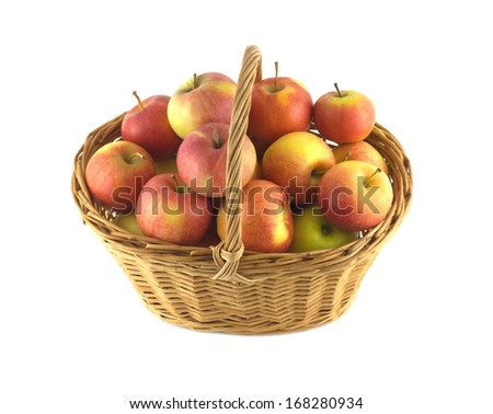 Brown wicker basket full of ripe apples isolated on white closeup