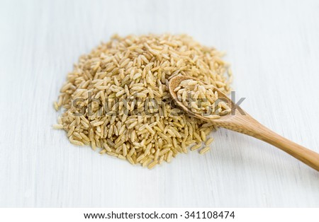 Brown wild rice and wooden spoon on a wooden background