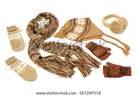 Brown winter accessories isolated on white background. Wool scarf, gloves, hat and earmuffs nicely arranged.  - stock photo