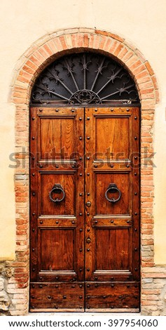 Brown wood old door in the centre of San Gimignano, Tuscany, Italy. - stock photo