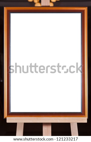 brown wood picture frame with white cut out canvas on easel