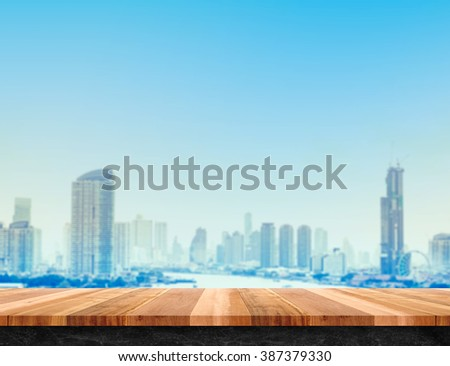 Brown wood plank table top and black marble base with city building landscape view, Mock up template for display or montage of your product, Urban concept background - stock photo