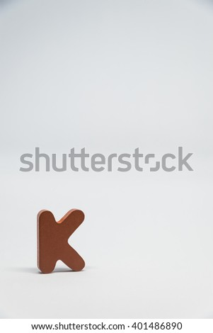 Brown Wooden alphabet K with white background in Vertical view - stock photo