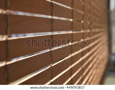 Brown wooden blinds rolled out and hanging outside a residential home