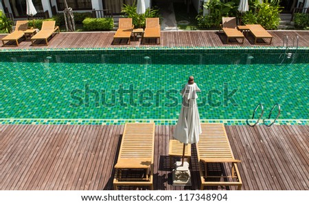 Brown wooden chairs side swimming pool. - stock photo