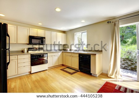 Brown wooden dining table in small kitchen room with black appliances and hardwood floor.