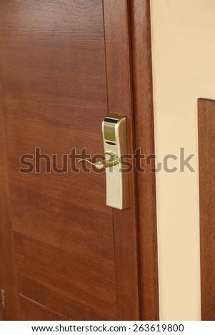 Brown wooden door with golden electronic lock - stock photo