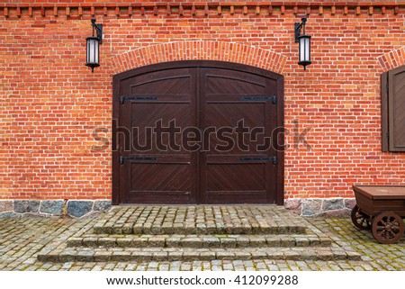 Brown wooden gate in the ancient building of red bricks - stock photo