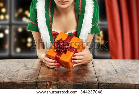 brown wooden table and elf and gift in hands of gold color  - stock photo