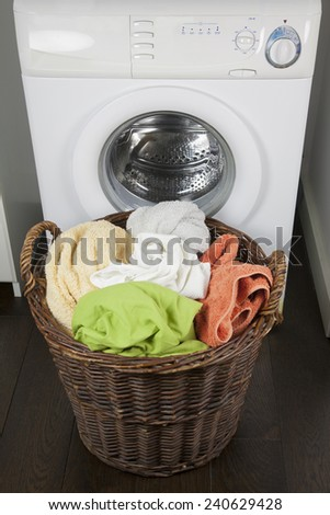brown wooden wicker basket full of dirty clothes sheets and towels at door of white washing machine