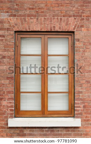 Brown wooden window on brick wall - stock photo