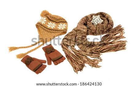 Brown wool scarf, a pair of gloves and a hat nicely arranged. Winter accessories isolated on white background. - stock photo