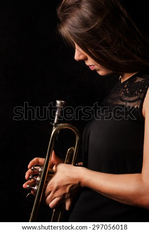 Brownhaired women in front of black backgound is looking on her trumpet