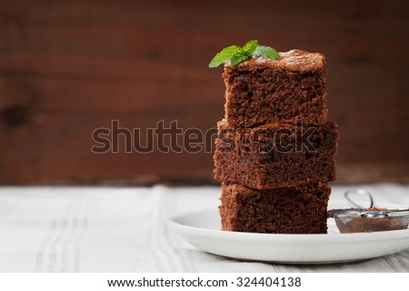 Brownie stack, closeup chocolate cake in plate on rustic wooden table - stock photo