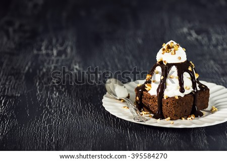 Brownie Sundae with a Scoop of Vanilla Ice Cream, Chocolate Sauce, Whipped Cream, and Nuts with Copy Space - stock photo