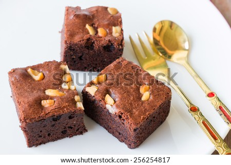 brownies and golden spoon with cup of coffee on table