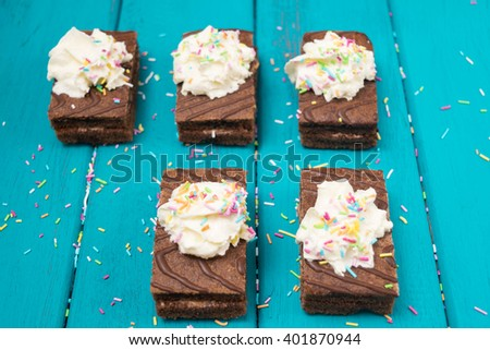 Brownies decorated with whipped cream and sugar frosting top view toned selective focus - stock photo