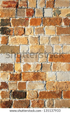 Brownish colored natural rough stone brick wall with harsh texture