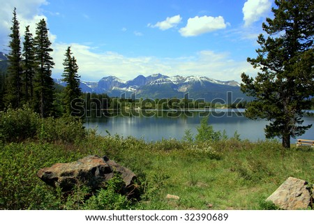 Bruce Mines Lake, southewestern Alberta, Canada; Rocky mountains in the background; spruce trees, green foliage and rocks in foreground. - stock photo
