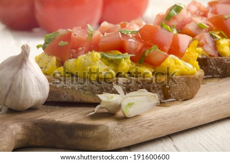 bruchetta with scrambled eggs, tomato, crushed pepper and garlic - stock photo