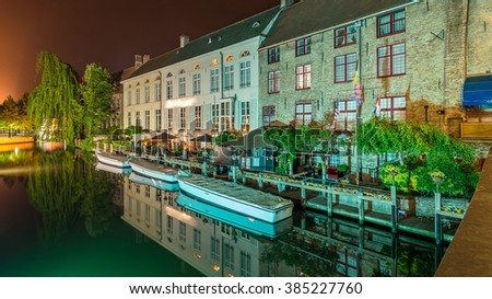 Bruges, Beautiful Scenic cityscape with a medieval Groenerei canal reflections, canal boat tour embankment jetty and the quay Dijver and Illuminated Church of Our Lady at night in summer, Belgium - stock photo