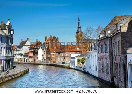 Bruges, Belgium - April 10, 2016: Panorama with canal and colorful traditional houses against cloudy blue sky in popular belgian destination, Brugge, Belguim