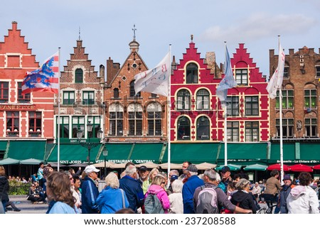 BRUGES, BELGIUM - 16 AUGUST 2014. Tourists walkins on Grote Markt  of Bruges, Brugge, meeting place of the Brugelings and tourists.  - stock photo