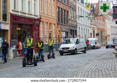 Bruges, Belgium - December 26, 2014: Tourists ride Segway on Christmas streets of city center. Bruges - one of the most beautiful and wonderfully preserved medieval cities in Europe.