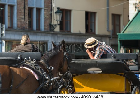 BRUGES, BELGIUM - JULY 3, 2015: A horse carriage awaits the arrival of new clients in one of the squares of the historic town.