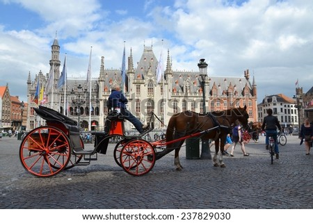 BRUGES, BELGIUM - JULY 15: Horse carriage on the Market square with the Provincial Hof (Province Court) in background on July 15, 2014 in Brussels, Belgium. - stock photo