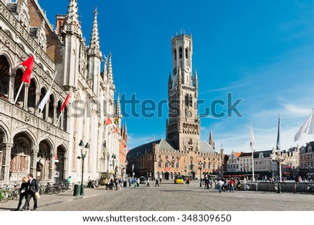 Bruges, Belgium - MAY 27, 2015: The Belfry Tower of Bruges. Tourists on Grote Markt square in Bruges, Belgium. Bruges is touristic center of Flanders city of Brugge, Belgium.