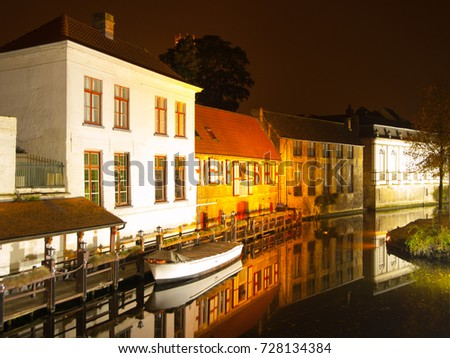 Bruges by night. Calm Dijver canal with boat in the dock. Belgium.