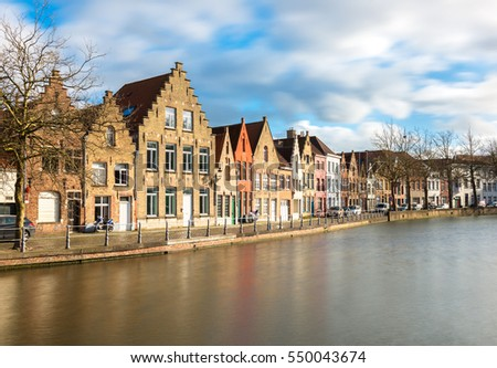 Bruges - February of 2016, Belgium: Old brick houses in traditional style and their reflections in water