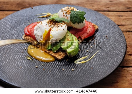Brunch Idea; Whole grain crispy bread spread with mustard and mayonnaise topped with slice avocado, tomato and poached egg. Garnished with parsley, grilled sesame seed, seaweed and chili powder. - stock photo