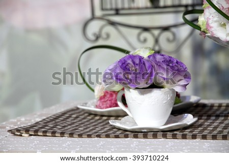 Brunch of blossom eustoma flowers in a white cup  - stock photo