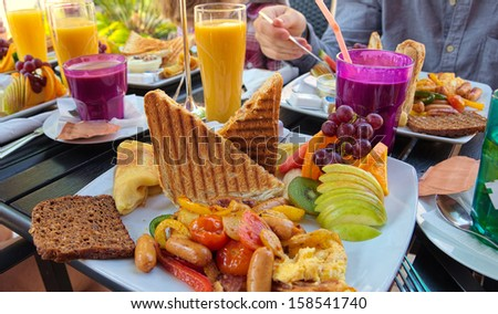 Brunch with sausages, tomatoes, fruit, toast, coffee and orange juice