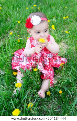 Brunette baby sitting in a field with dandelions - stock photo