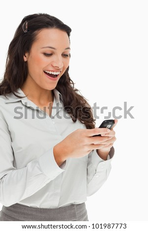 Brunette beaming while using her mobile against white background