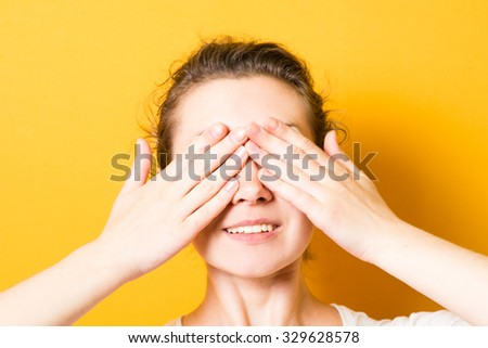 brunette beautiful girl closes eyes with her hands - stock photo